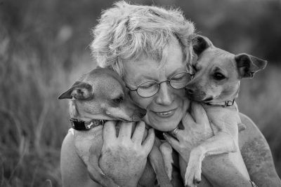 Dogs and Their Families, pet photographer Craig Holmes captures a loving portrait photograph of embrace of two dogs by their owner.